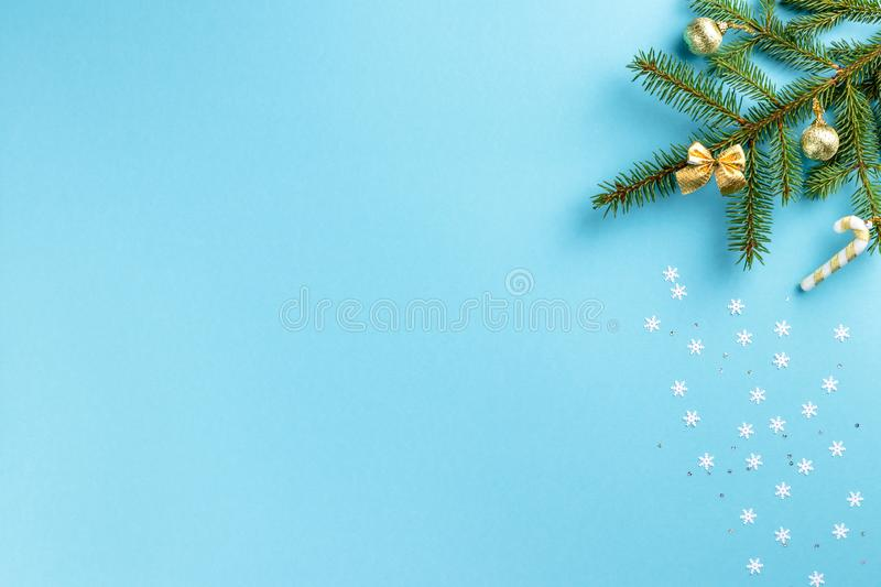 Christmas and winter composition. Frame made of fir branch, golden toys and white snowflakes with tinsel on pastel blue background royalty free stock images