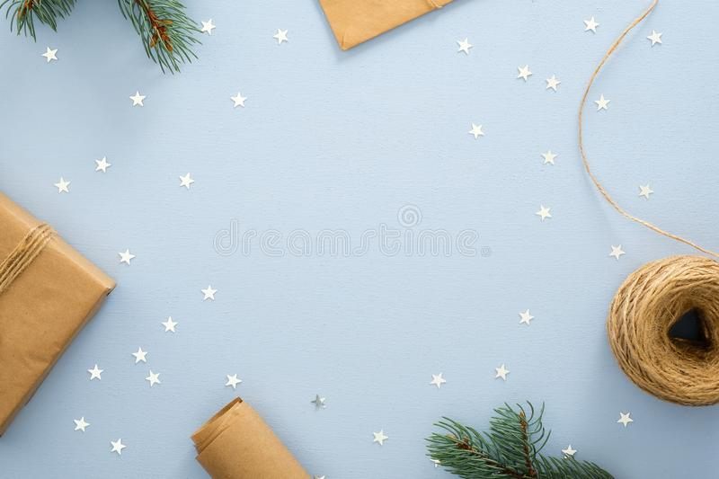 Christmas or winter composition. Frame made of gift box, wrapping paper, twine rope, glitter confetti on pastel blue background. royalty free stock photo