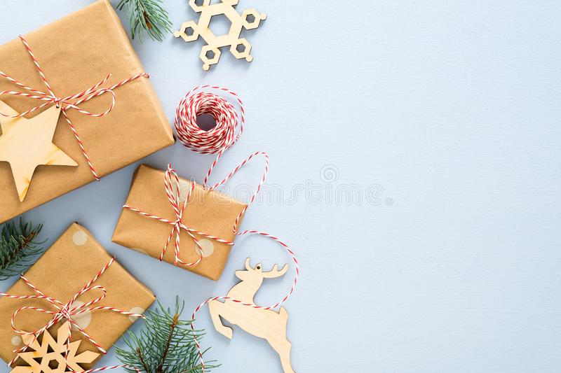 Christmas or winter composition. Frame made of gifts box wrapped kraft paper, twine rope, wooded Xmas decorations, fir tree royalty free stock image