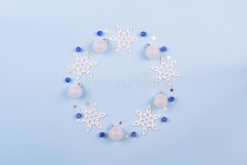 Christmas or winter composition. Snowflake, blue berries and decoration bals wreath on pastel blue background. Christmas, winter, stock image