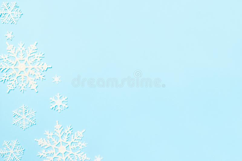 Christmas or winter composition. Snowflakes decoration on blue pastel background. Flat lay, top view, copy space royalty free stock image