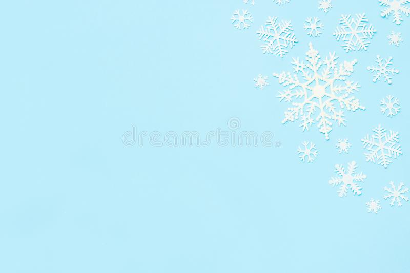 Christmas or winter composition. Snowflakes decoration on blue pastel background. Flat lay, top view, copy space stock photos