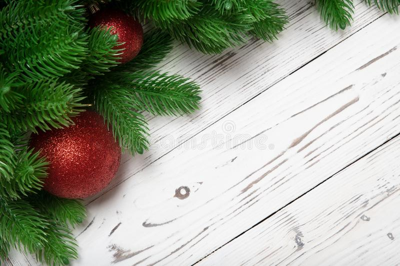 Christmas winter decoration with fir branches and red ball or baubles on wooden white board background royalty free stock photos