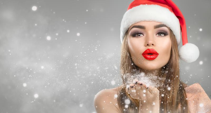 Christmas winter fashion girl on holiday blurred winter background. Beautiful New Year and Xmas holiday makeup. Beauty model woman in Santa`s hat blowing snow royalty free stock images