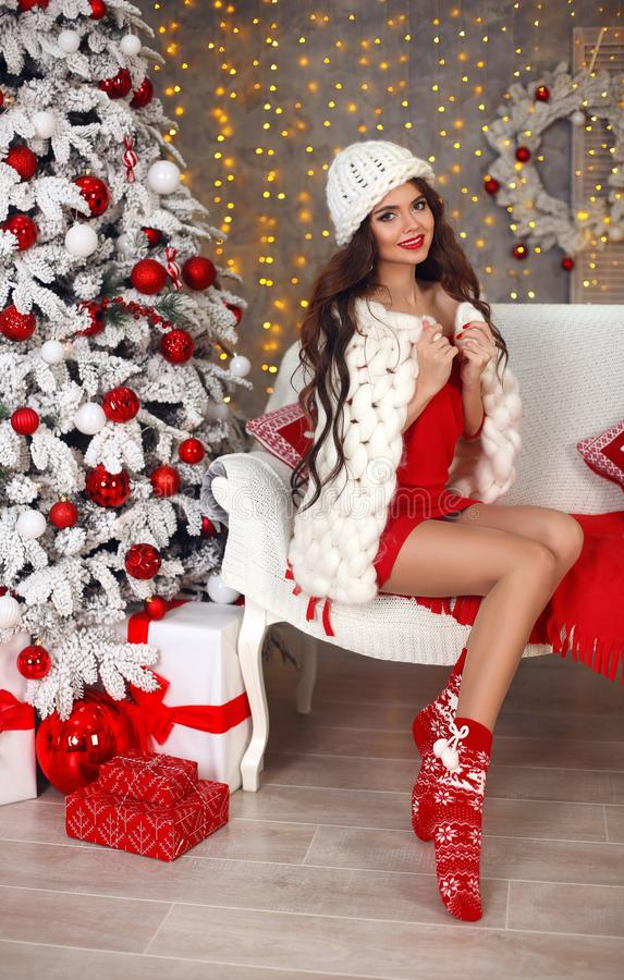 Christmas winter girl. Beautiful Cozy Woman with warm soft hat covered wool knitted marino blanket. Young attractive brunette in. Home over xmas tree lights stock image