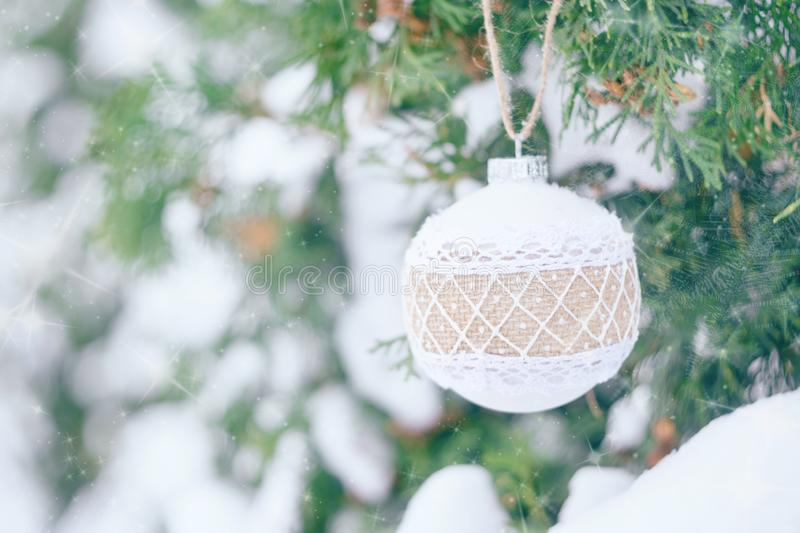 Christmas winter holiday greeting card. White rustic Christmas ornament ball with burlap on green christmas trees with snow. Festive outdoor background. Xmas royalty free stock photography