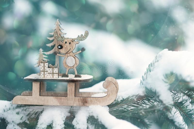 Christmas winter holiday greeting card. Wooden cute reindeer on sled, red gift boxes on white snow. And green christmas trees outdoor. Christmas composition royalty free stock photos