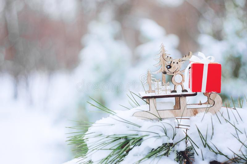 Christmas winter holiday greeting card. Wooden cute reindeer on sled, red gift boxes on white snow and green christmas trees outd. Oor. Christmas composition stock photo