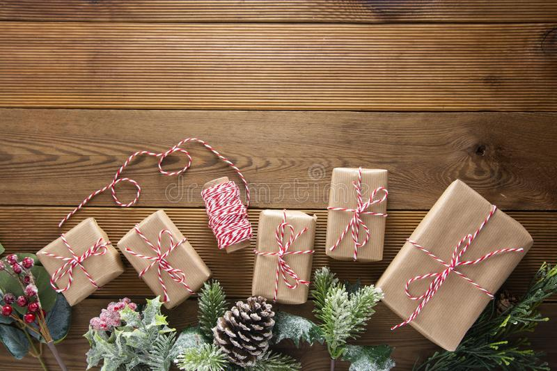 Christmas and winter holidays background. Christmas gift box with pine cones, fir brances, on brown wood table with copy space. stock photos