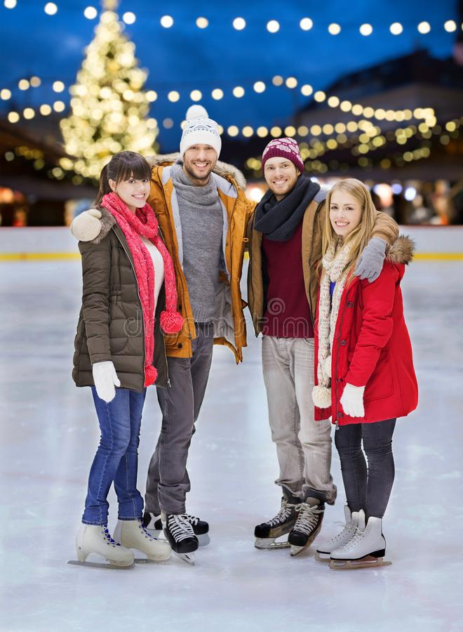 Happy friends at christmas skating rink. Christmas, winter and leisure concept - happy friends holding hands on skating rink over outdoor holiday lights stock photos