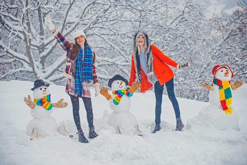 Christmas winter people. Girls playing with Snowman -  on snow background. Funny winter people Portrait. stock images