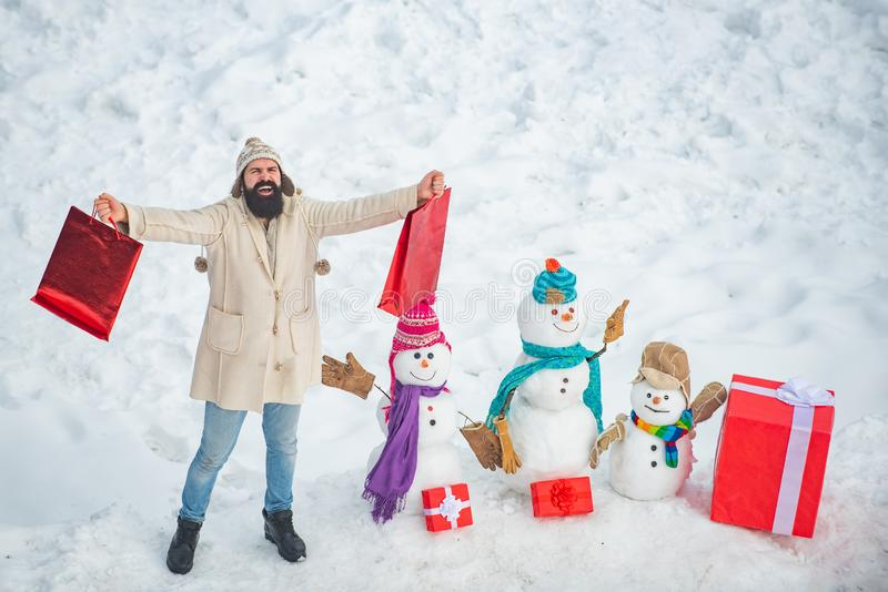Christmas winter people portrait. Christmas preparation - funny bearded man with red gift box make snowman. Happy winter stock photo