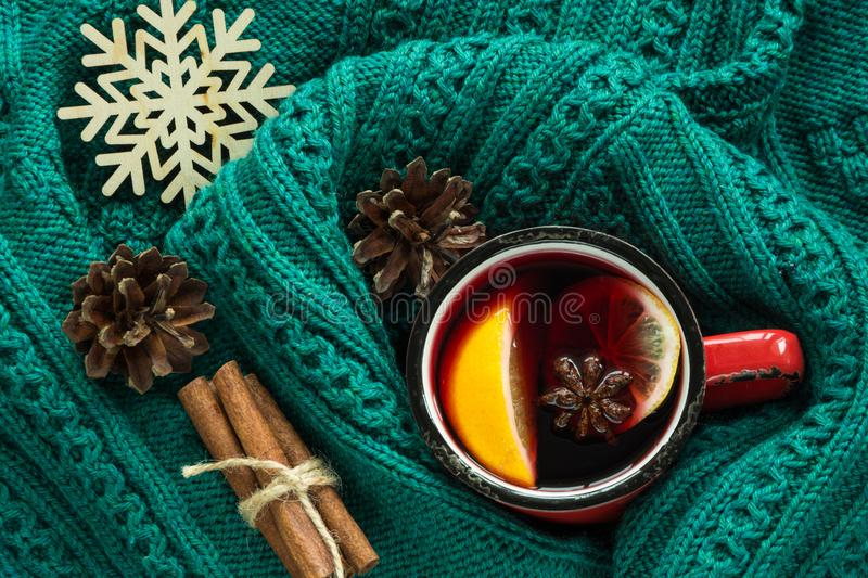 Christmas and winter traditional hot beverage. Mulled wine in red mug with spice wrapped in warm green sweater. stock photo