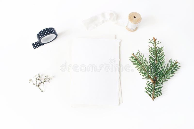 Christmas, winter wedding desktop stationery mock-up scene. Blank greeting card, envelope, black washi tape, silk ribbon stock photo
