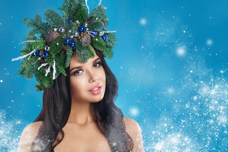 Christmas Winter Woman. Beautiful New Year and Christmas Tree Holiday Hairstyle and Make up. Beauty Fashion Model Girl over Snow stock photo