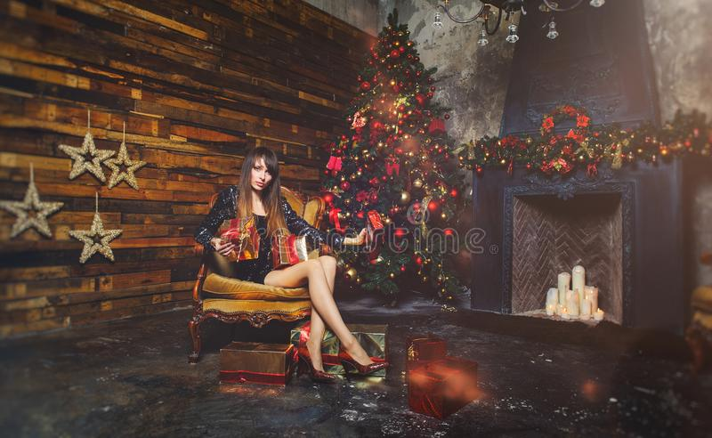 Christmas winter woman with christmas presents. Fairy Beautiful Christmas and Christmas tree Festive make-up. Fashion model girl w royalty free stock photo