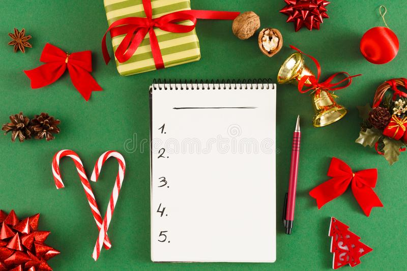Christmas wish list. Empty notepad at messy table background stock photos