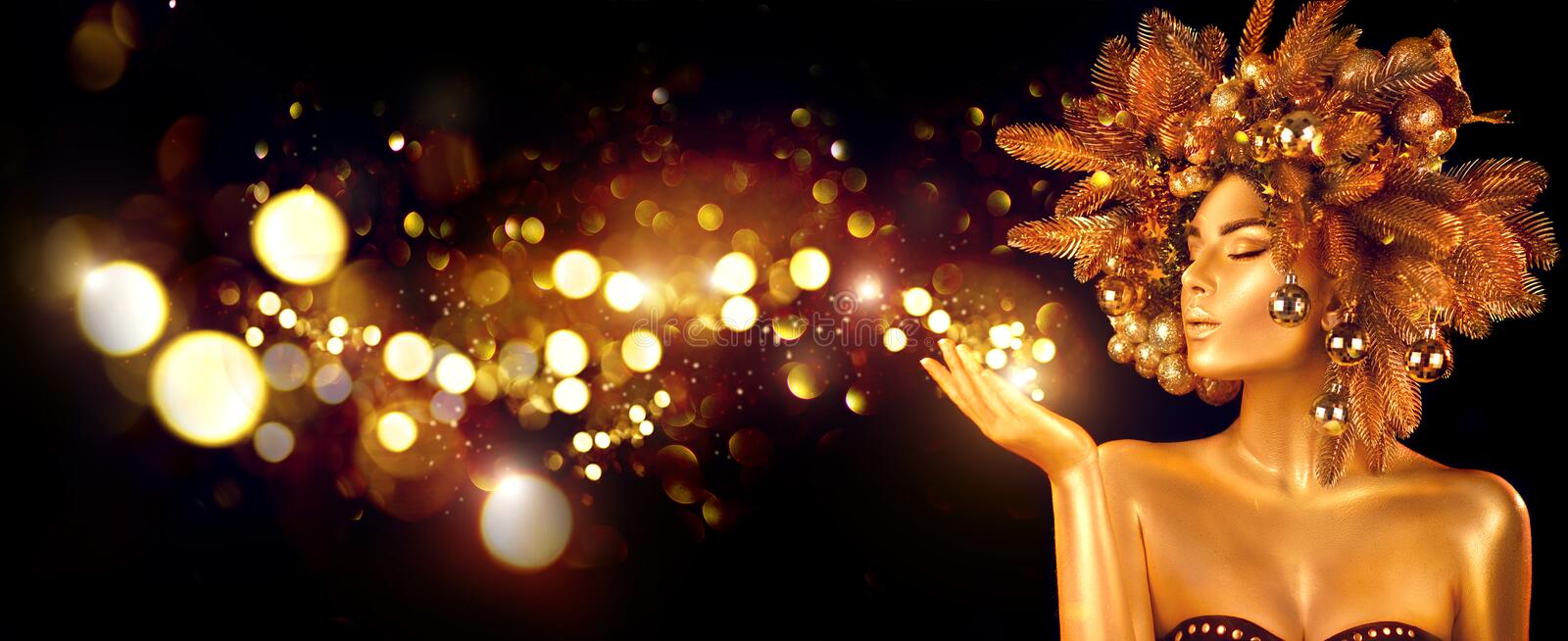 Christmas Wish. Winter Woman with Magic in Her Hand. Beautiful Christmas Tree Holiday Hairstyle and gold skin Makeup royalty free stock images