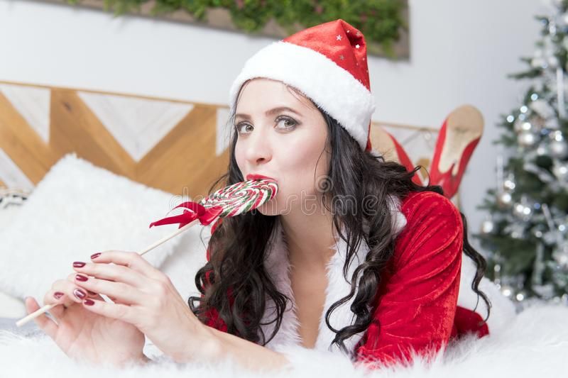 Christmas woman. Beauty model girl in Santa Claus hat with red lips and xmas lollipop candy in her hand. Joy. Surprised expression stock photo