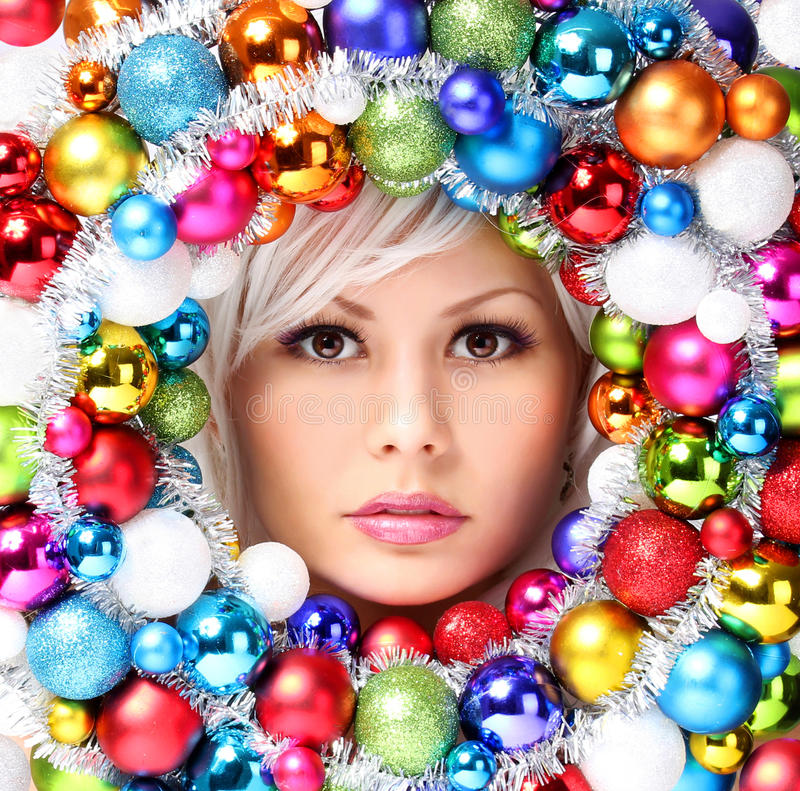 Christmas Woman with Colored Balls. Face of Beautiful Girl. With Fashion Makeup and Shiny Christmas Baubles stock image