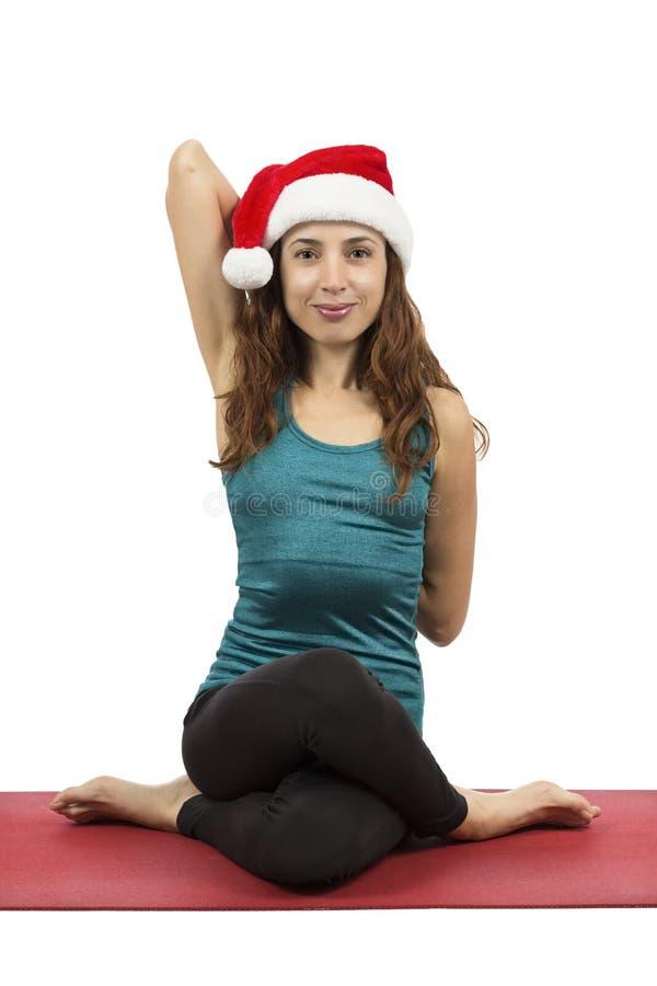 Christmas woman doing Cow Face pose in yoga. Young yogi caucasian christmas woman with santa hat doing cow face pose in yoga royalty free stock photography