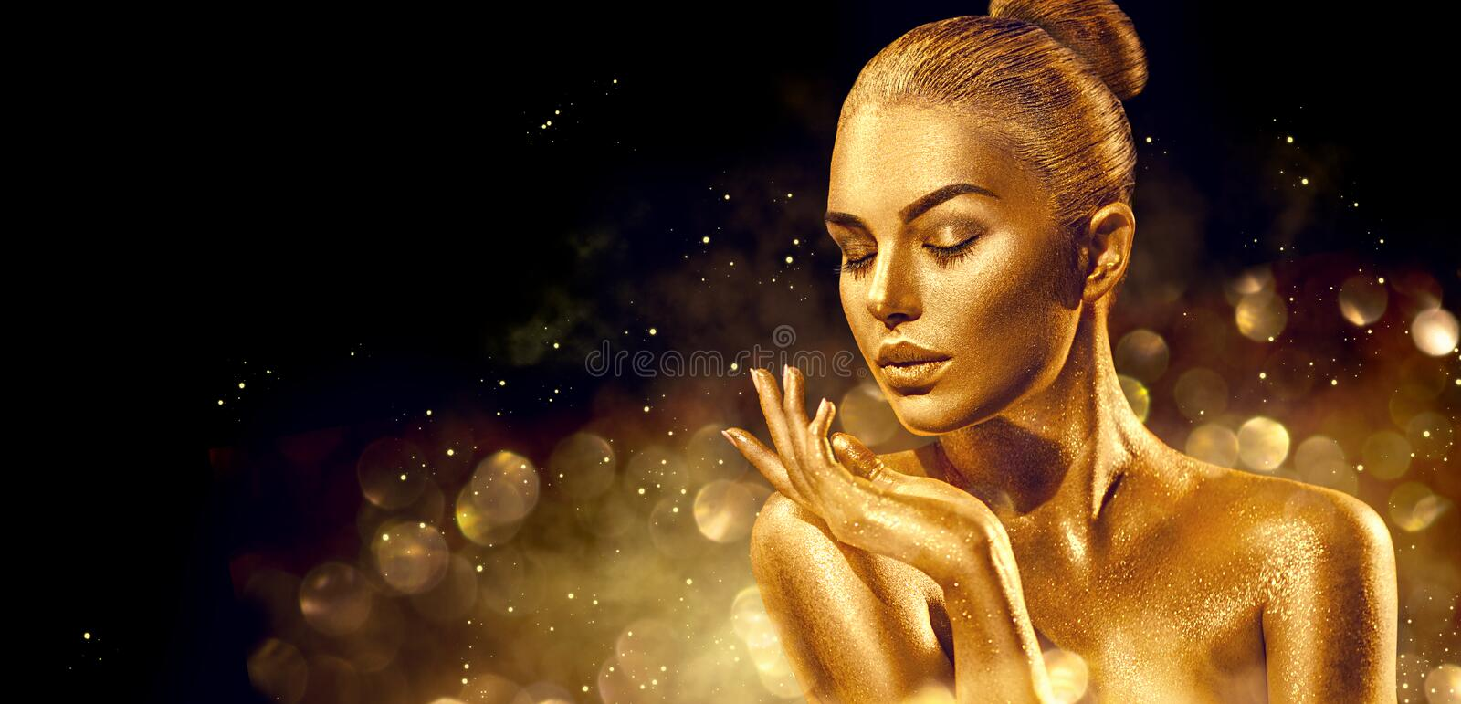 Christmas woman. Golden skin woman portrait closeup. model girl with holiday golden shiny professional makeup. Golden metallic body royalty free stock photo