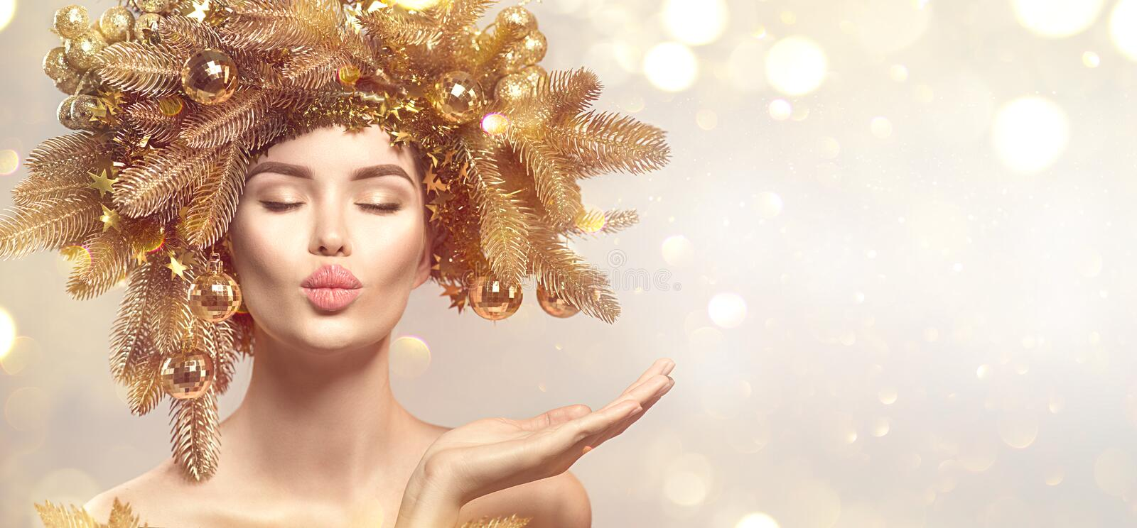 Christmas Woman with golden spruce tree wreath hairstyle on blurred pastel background. Beautiful Xmas model girl royalty free stock photos