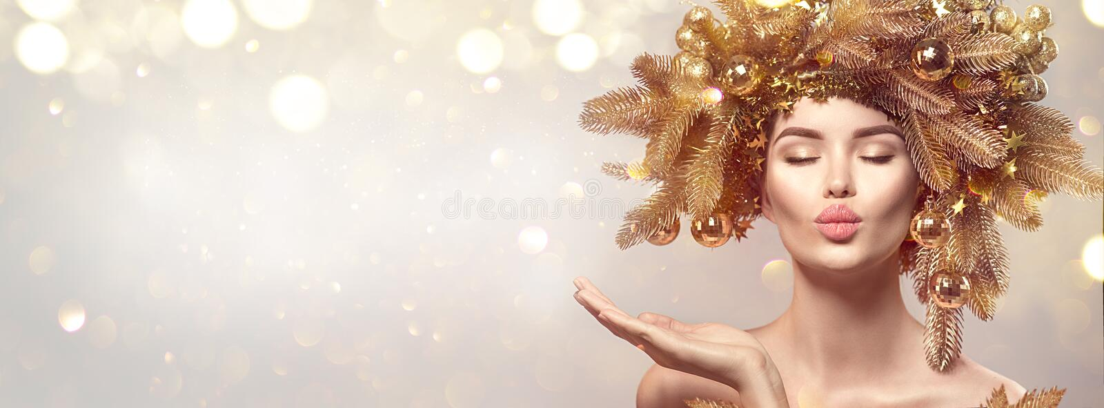 Christmas Woman with golden spruce tree wreath hairstyle on blurred pastel background. Beautiful Xmas model girl royalty free stock photography