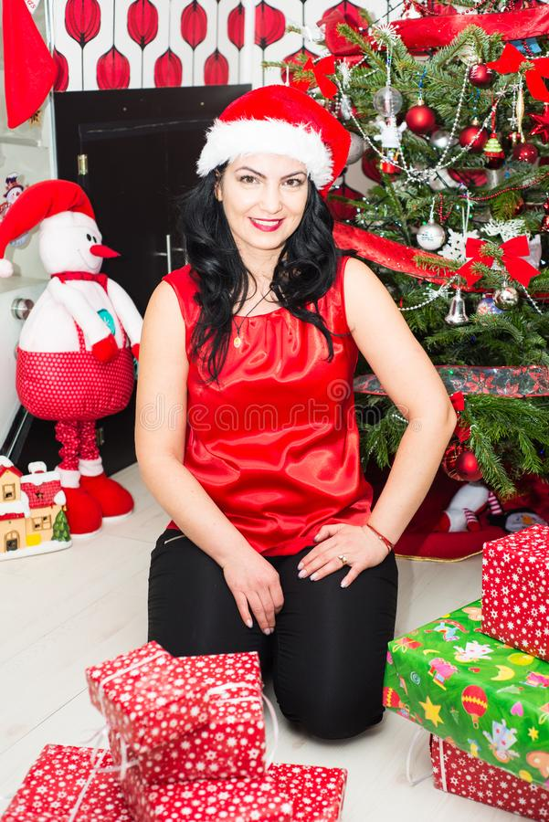 Christmas woman in her house. Beautiful woman in red posing home in front of Christmas tree woth presents stock images
