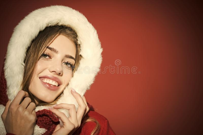 Christmas woman in red hood, copy space. New year and christmas. Happy girl celebrate new year on red background. Xmas party and winter holiday. Woman in santa royalty free stock image