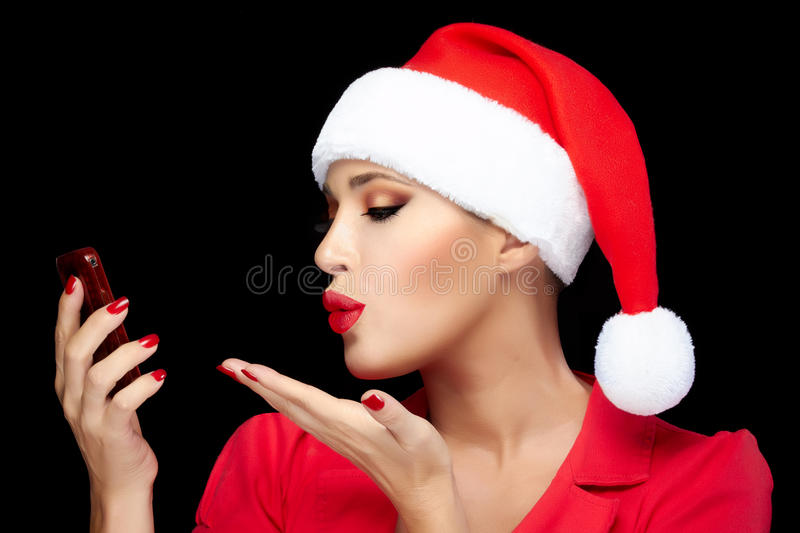 Christmas Woman in Santa Hat Taking a Selfie Sending Kisses. Merry Christmas. Beautiful Christmas girl in Santa hat makes a selfie sending kisses with a stock image