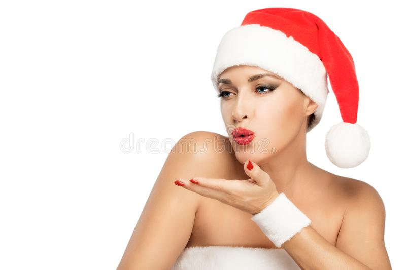 Christmas woman sending kiss with red juicy lips and matching nails. Attractive female in Santa hat looking away and sending kiss to empty space on white stock photos