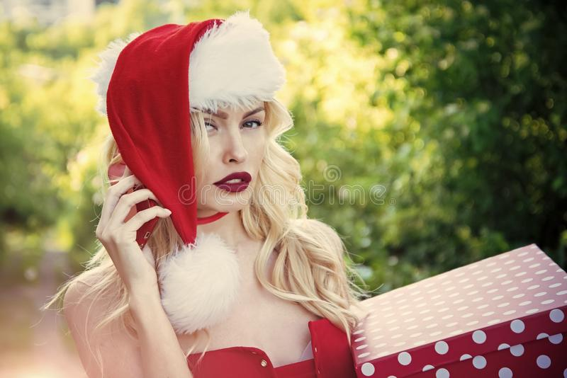 Christmas woman with red lips, black Friday. Girl celebrate new year with present box, mobile phone. Woman in santa hat with gift, greeting. Xmas party, winter royalty free stock images