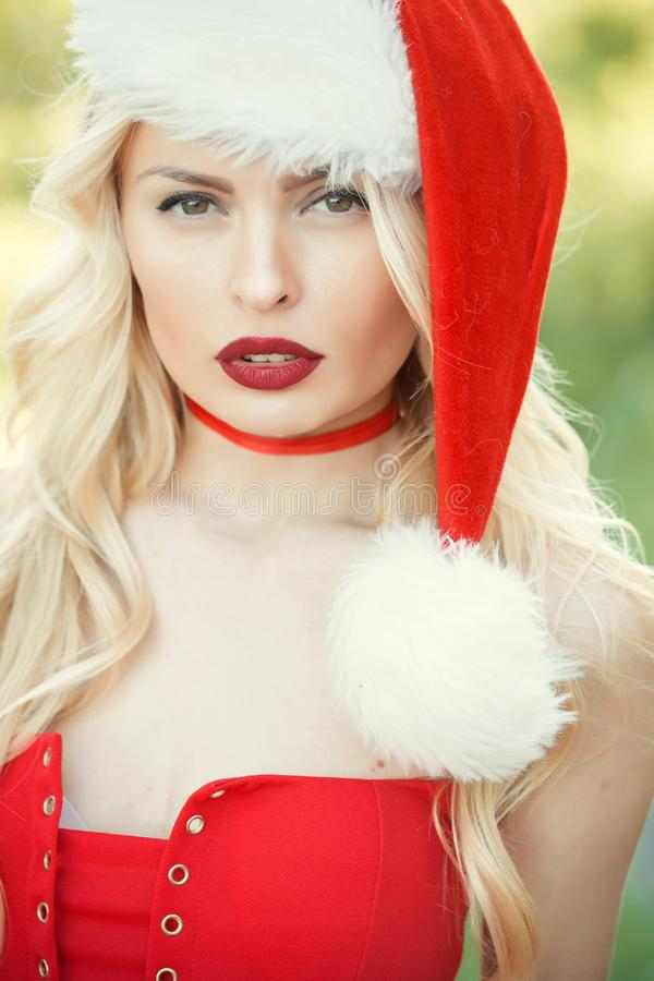 Christmas woman with red lips. Woman in santa hat, greeting and preparation. Christmas time. Xmas party, winter holiday. girl celebrate new year stock photography