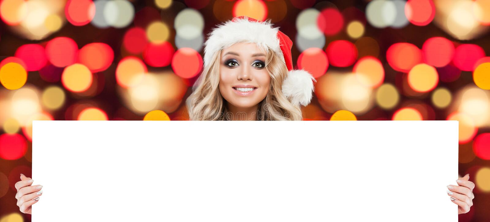 Christmas woman showing white big blank board background. With copy space for advertising marketing or product placement on abstract bokeh glitter stock photo