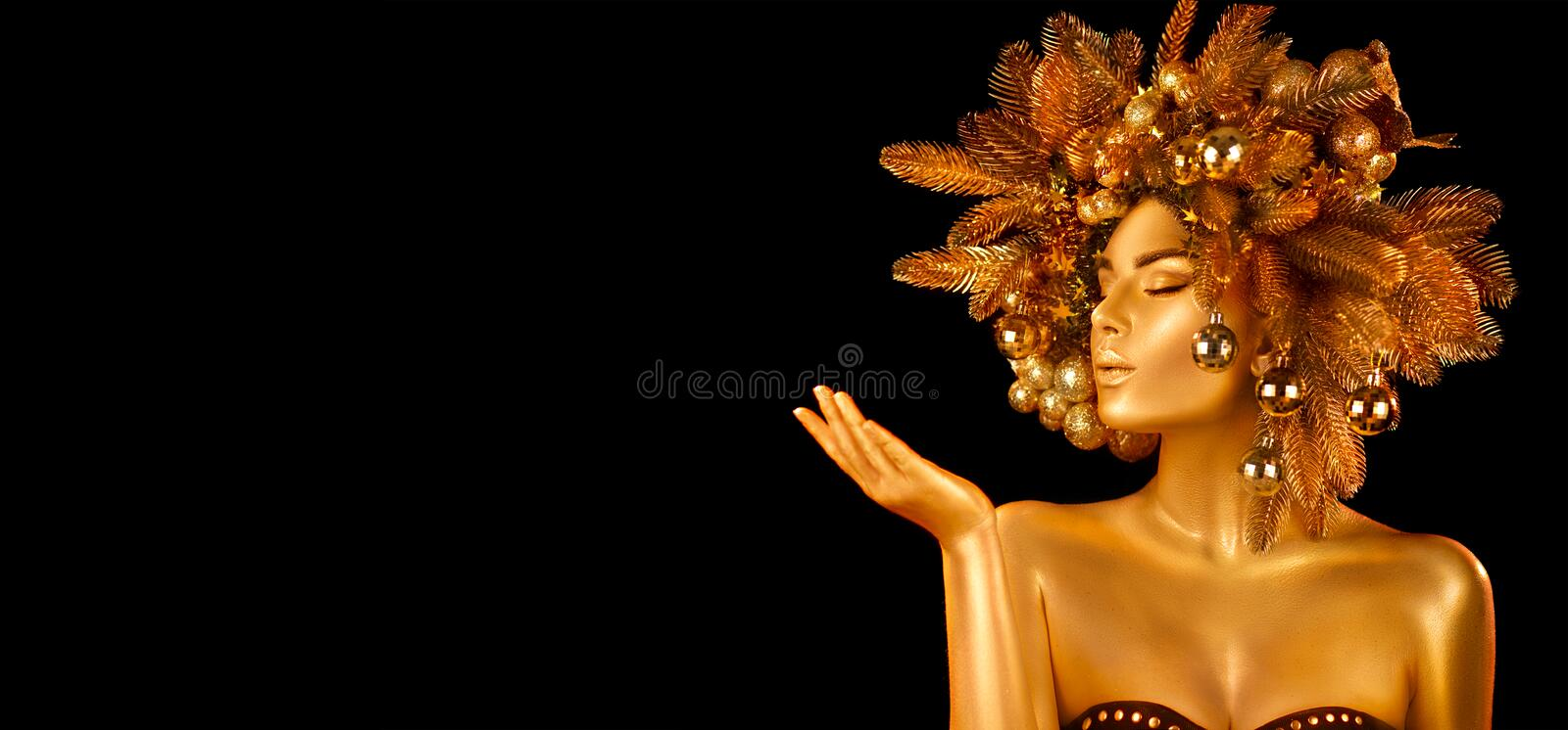 Christmas Woman. Winter girl pointing Hand, holding product. Holiday Hairstyle and gold skin Makeup. Girl in decorated Xmas wreath stock photo