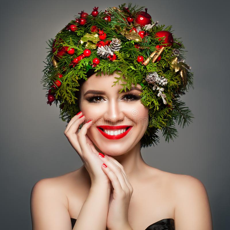 Christmas Woman with Xmas Wreath, Makeup. And Manicured Hands. Smiling Model Woman Christmas Concept royalty free stock image