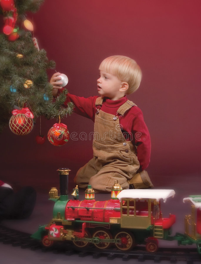 Christmas Wonderment. Little boy focused on a Christmas ornament