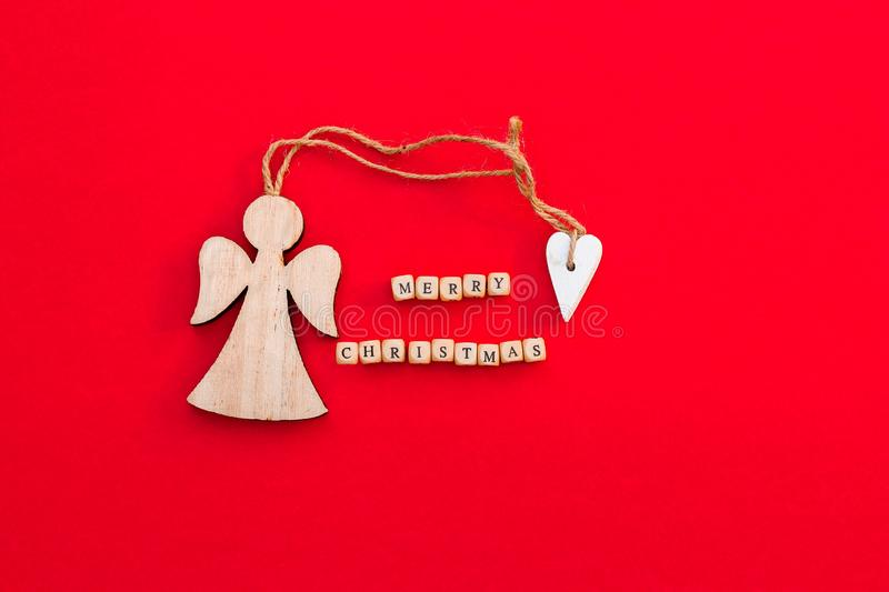 Christmas wooden angel with heart and twine with words Merry Christmas on little bricks on bright red background. Minimalism concept. Natural eco materials New stock photo