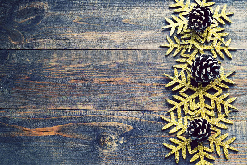 Christmas wooden background with decorative snowflakes and pine cones. View with copy space. Snowflakes on a wooden board. Empty space for your text royalty free stock photography