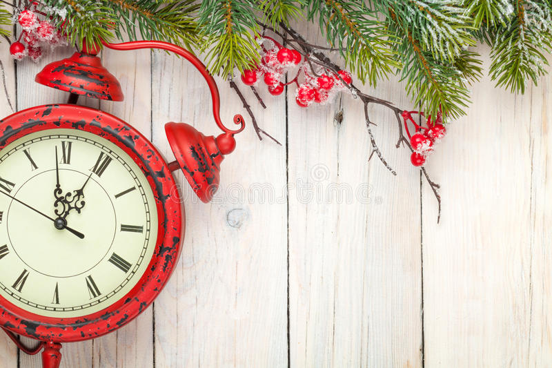 Christmas wooden background with fir tree and antique alarm clock stock photo