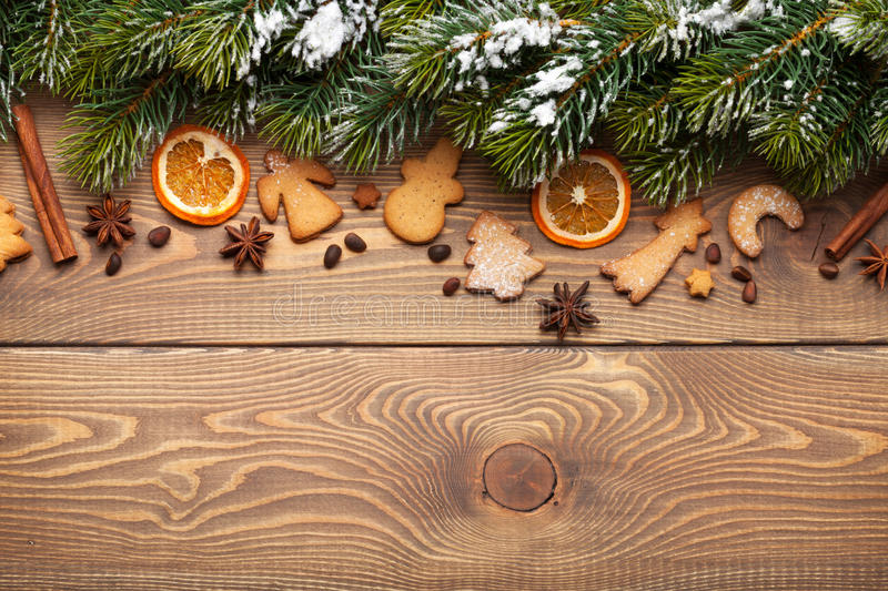 Christmas wooden background with snow fir tree, spices and gingerbread cookies stock images