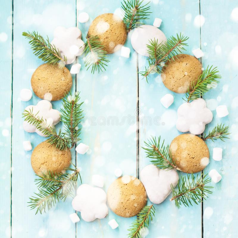 Christmas wooden background with tree branches, gingerbread and marshmallows decorated with snow stock photos