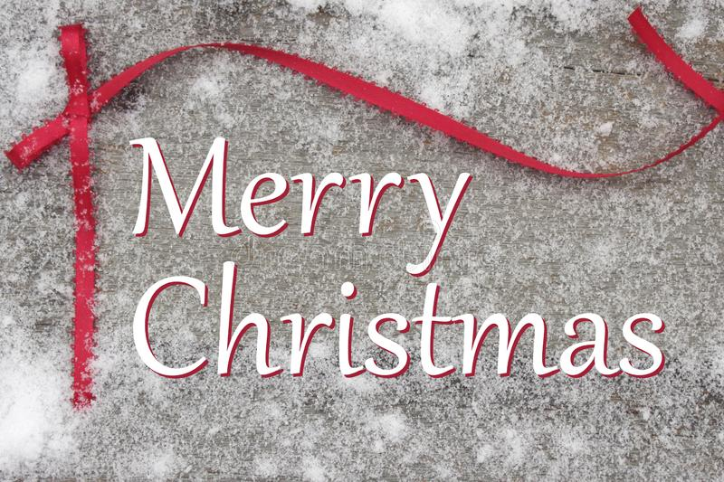 Christmas words on wooden snow covered board with red ribbon. Merry Christmas words with red ribbon bow on snowy rustic board stock photo