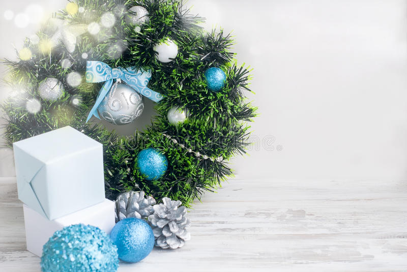 Christmas wreath blue, silver and white color. Christmas decoration wreath with blue and silver boll, toys and ribbon on the white wooden background. Copy space stock photography