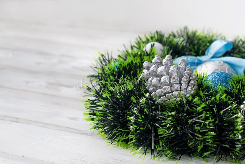 Christmas wreath blue, silver and white color. Christmas decoration wreath with blue and silver boll, toys and ribbon on the white wooden background. Top view royalty free stock photography