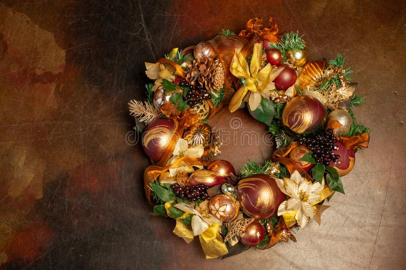 Christmas wreath on brown background with copyspace. Wreath decorated with balls and bows of gold and brown, with green leaves stock image