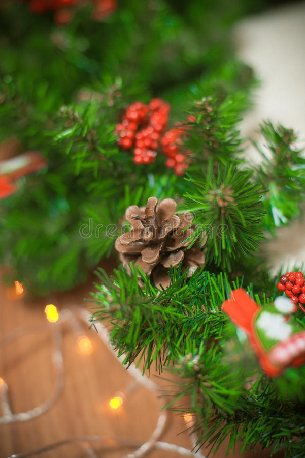 Christmas wreath of coniferous branches with cones and red berries and a garland of lights stock photo