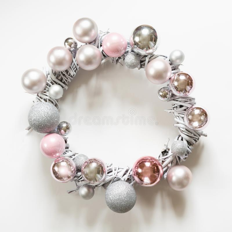 Christmas wreath of decor, silver and pink balls, painted vine on white. Top view stock images