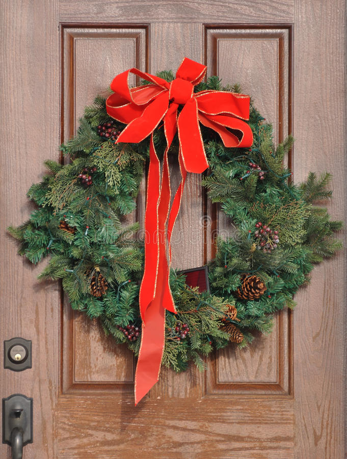 Christmas Wreath on a Door. Christmas Wreath with Red Bow on a Door stock photo